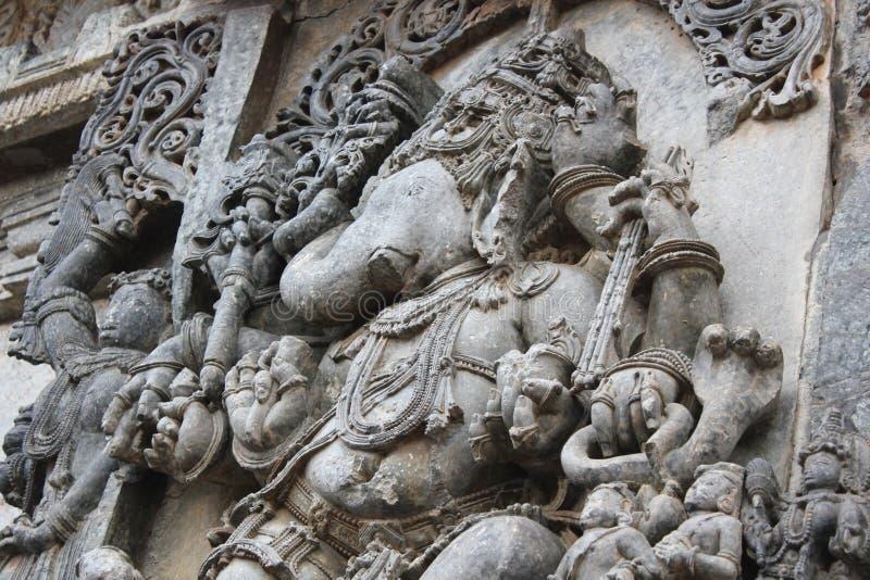 Snida för Hoysaleshwara tempelvägg av valampurien som är vinayagar - elefantgud med stammen som snidas till rätsidan royaltyfria foton