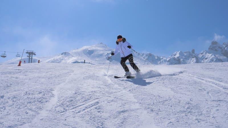 Snida för kvinnaskidåkare går ner Ski Slope Of The Mountain arkivbild