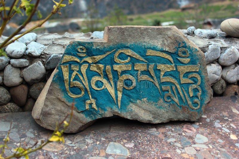 Sniden sten med inskriften Om Mani Padme Hum fotografering för bildbyråer