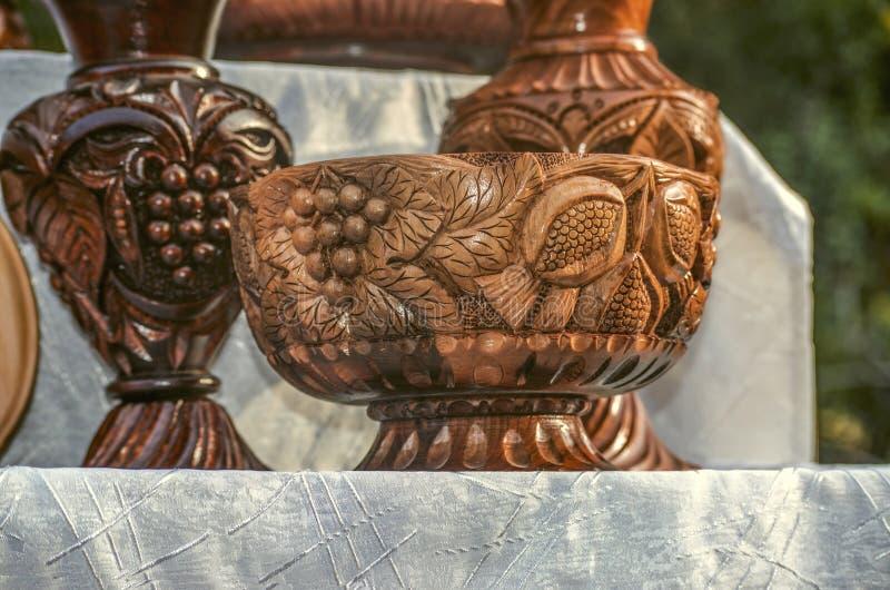 Snidit i trävasen för traditionell stil på ett ben med en modell av druvor och granatäpplet på en filial med sidor och täckt arkivfoto