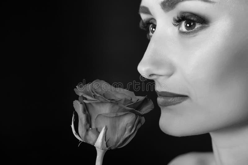 Sniff γυναικών αυξήθηκε, μαύρο διάστημα αντιγράφων υποβάθρου Η κυρία με το makeup απολαμβάνει στενό επάνω λουλουδιών Τι είδους fl στοκ φωτογραφίες
