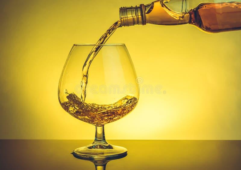 Snifter бармена лить рябиновки в элегантном типичном стекле коньяка на таблице стоковая фотография