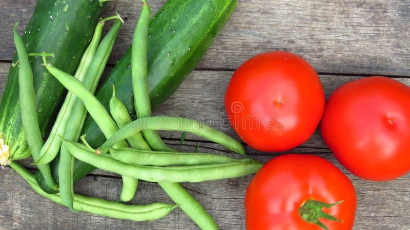 Snijboon/witte nier verse boon-peulen, komkommers en tomaten op rustieke houten achtergrond royalty-vrije stock foto