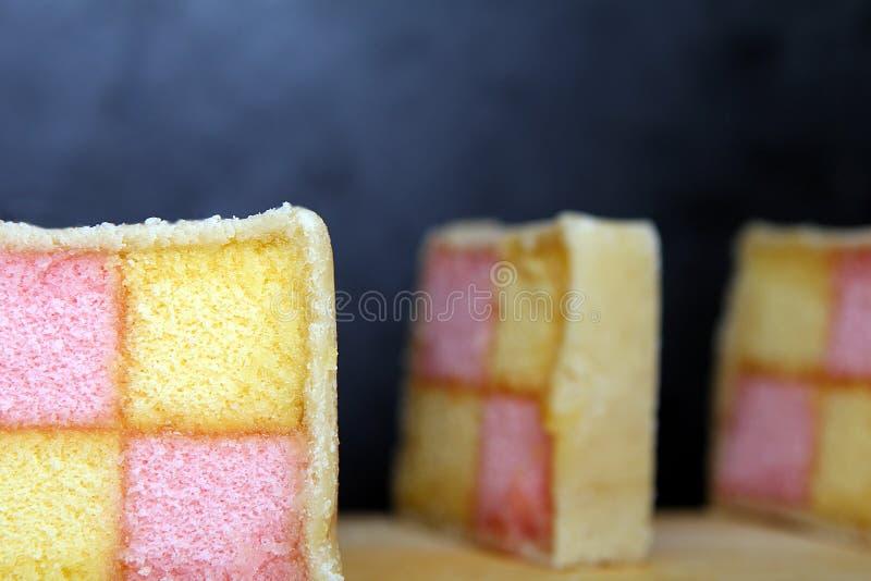 Snijd Battenberg-vers Cakeplakken op houten raad met donkere achtergrond Roze en gele die spons in marsepein wordt behandeld royalty-vrije stock afbeeldingen