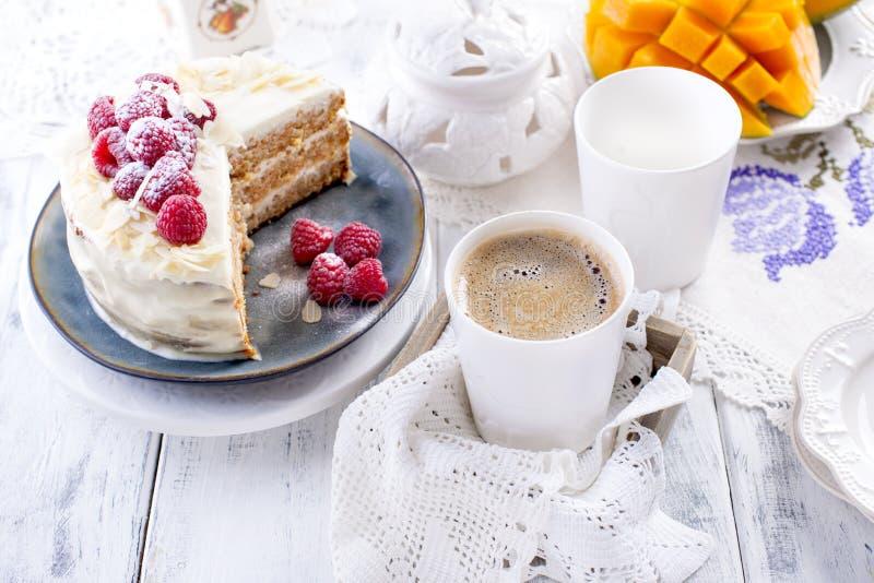 Snijd de cake met witte room, voor het fruit van de ontbijta mango Witte achtergrond, tafelkleed met kant, een kop van geurige zw royalty-vrije stock afbeelding