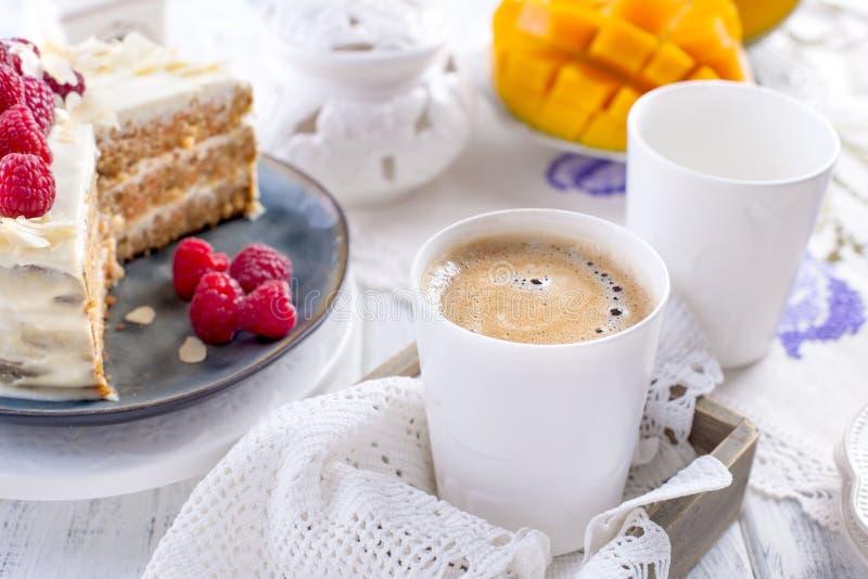 Snijd de cake met witte room, voor het fruit van de ontbijta mango Witte achtergrond, tafelkleed met kant, een kop van koffie en  stock fotografie