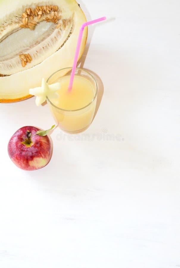 Snijd de meloen naast de rode appelen, een glas van smoothie met een plak van meloen met een stro royalty-vrije stock foto's