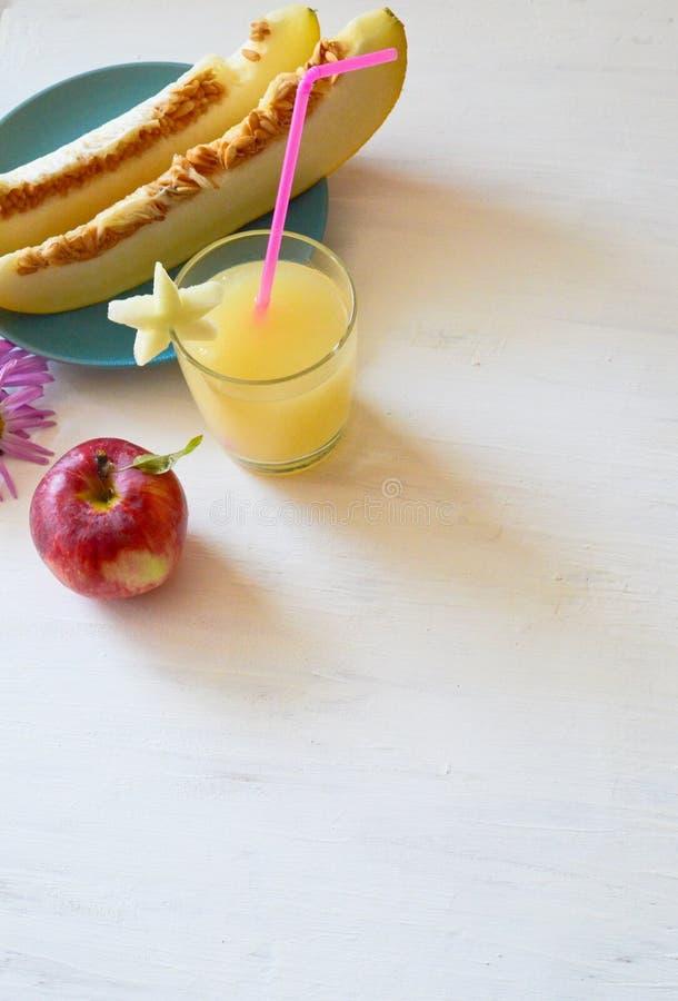 Snijd de meloen naast de rode appelen, een glas van smoothie met een plak van meloen met een stro royalty-vrije stock foto