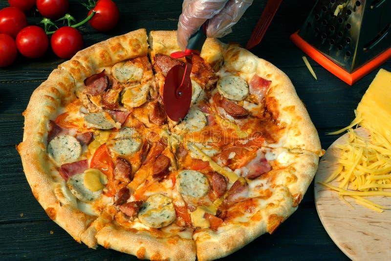 Snijd pizza, op plakken, met worst, tomaat en kaas, met speciaal mes af - snijderswiel Op houten lijst ook zijn er royalty-vrije stock foto