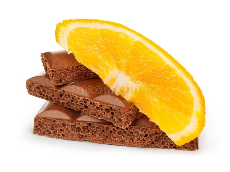 Snijd ruwweg brokken van een chocoladereep met oranje fruit royalty-vrije stock foto