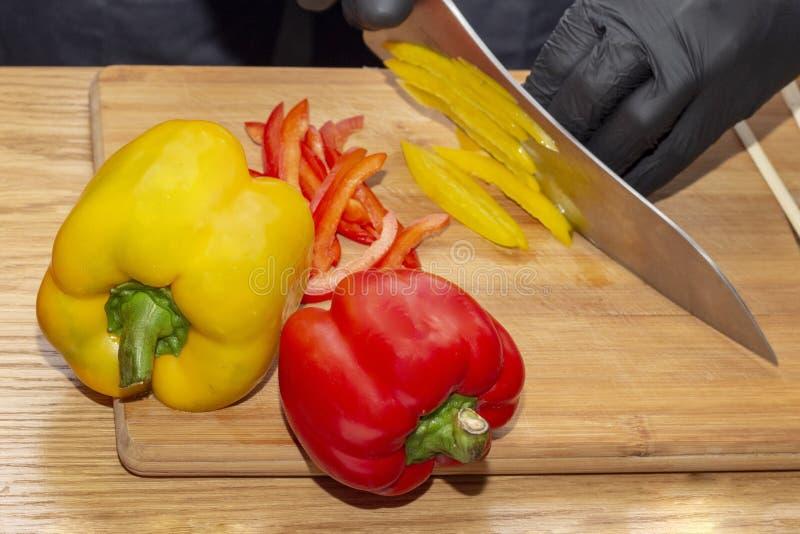 Snijdende paprikakok het kokende gezonde gezonde voedsel van het voedseldieet de houten scherpe raad op houten lijst, chef-kok di stock fotografie