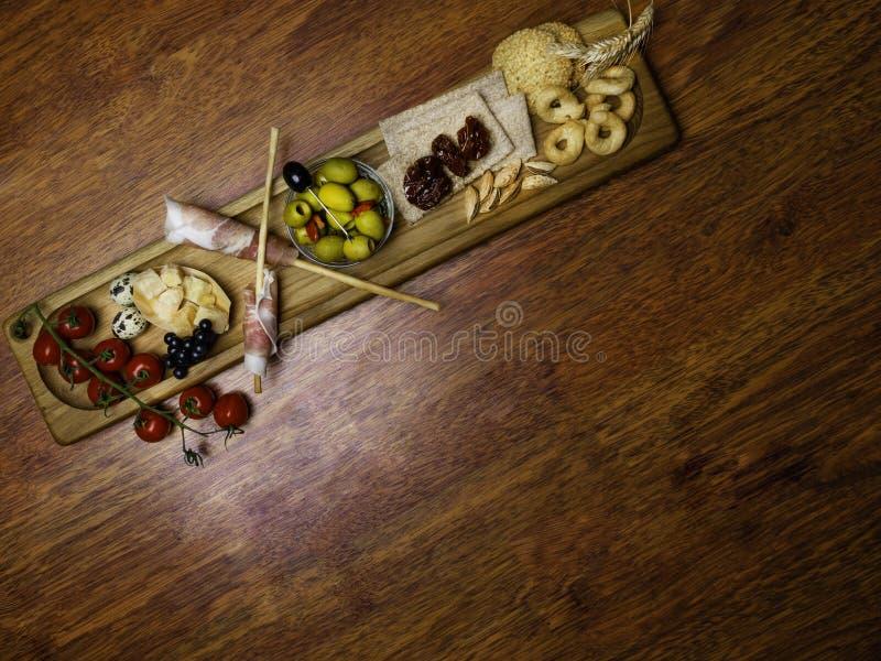 Snijdt het koude vlees van de Antipastoschotel met de stokken van het grissinibrood, prosciutto, parmezaanse kaas, olijven, droge royalty-vrije stock afbeelding