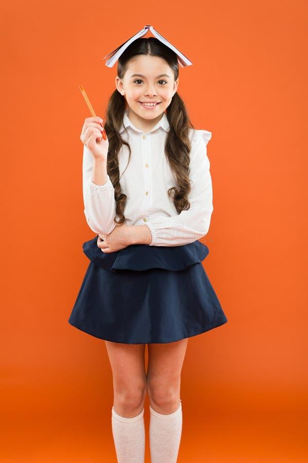 Snille mot okunnighet Fick det lilla skolbarnet för snille en ljus idé på orange bakgrund Liten flickainnehavbok på arkivfoton
