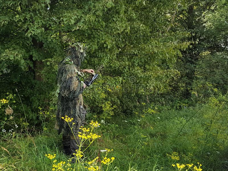 A sniper in a camouflage suit takes revenge on a sniper rifle. A soldier in camouflage is standing in the midst of green bushes. stock photos