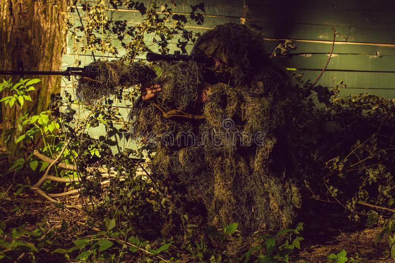 Sniper in ghillie suit. Sniper soldier in ghillie suit camo and mask sitting with rifle aiming target near tree and green branches background stock photography