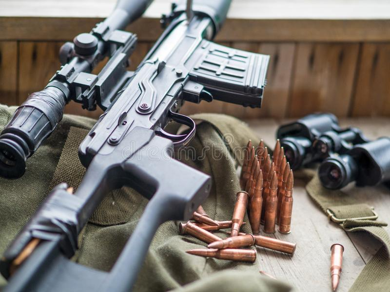 Sniper rifle, bunoculars and ammo laying on wooden floor stock photo