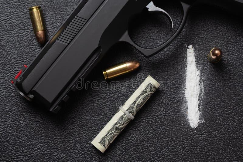Snirkel för dollarräkning, kokainpulver, pistol och tre kulor på svart yttersida royaltyfria foton