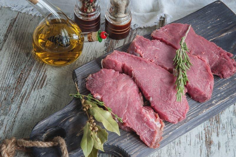Snitt av nötkött för att grilla på en träskärbräda med lagerbladen, rosmarinen, olivoljan och de Provencal örterna för marinaden  royaltyfri bild