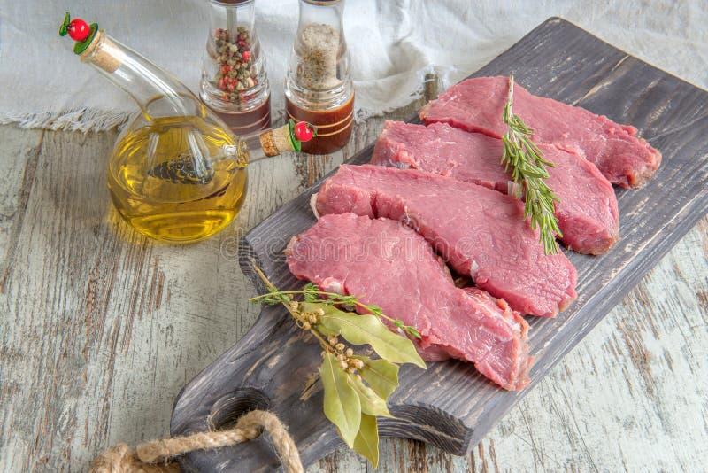 Snitt av nötkött för att grilla på en träskärbräda med lagerbladen, rosmarinen, olivoljan och de Provencal örterna för marinaden  royaltyfri foto