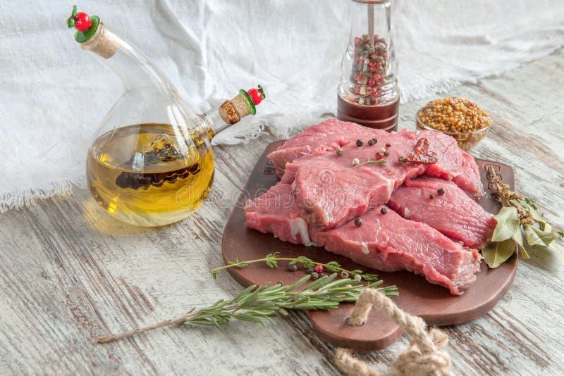 Snitt av nötkött för att grilla på en träskärbräda med lagerbladen, rosmarinen, olivoljan och de Provencal örterna för marinaden  arkivbild