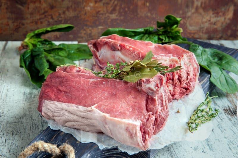 Snitt av nötkött för att grilla på en träskärbräda med spenat, rosmarin och Provencal örter för marinaden i en lantlig stil royaltyfria bilder