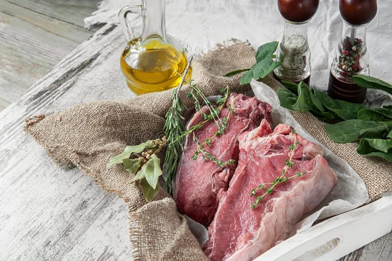 Snitt av nötkött för att grilla på en träskärbräda med spenat, rosmarin och Provencal örter för marinaden i en lantlig stil royaltyfria foton