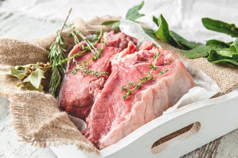 Snitt av nötkött för att grilla på en träskärbräda med spenat, rosmarin och Provencal örter för marinaden i en lantlig stil royaltyfri fotografi