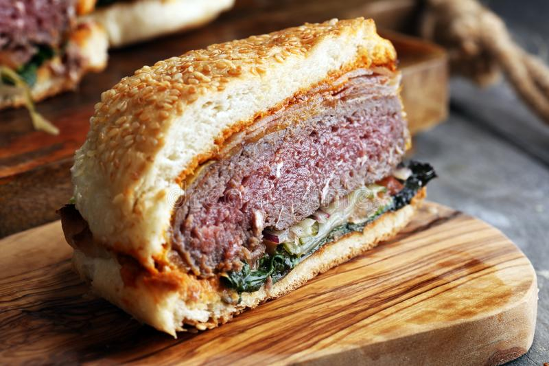 Snitt i den halva angus hamburgaren på kornbullen med tomatnjutningen, lettuc royaltyfria bilder