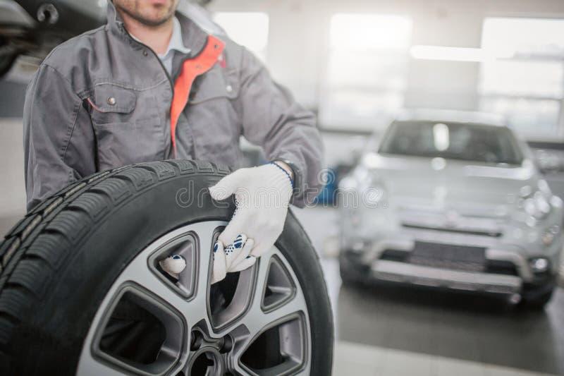 Snittsikt av arbetaren i grått enhetligt ställnings- och hållbilhjul med båda händer Han bär vita handskar Ny bil in bakom arkivbild
