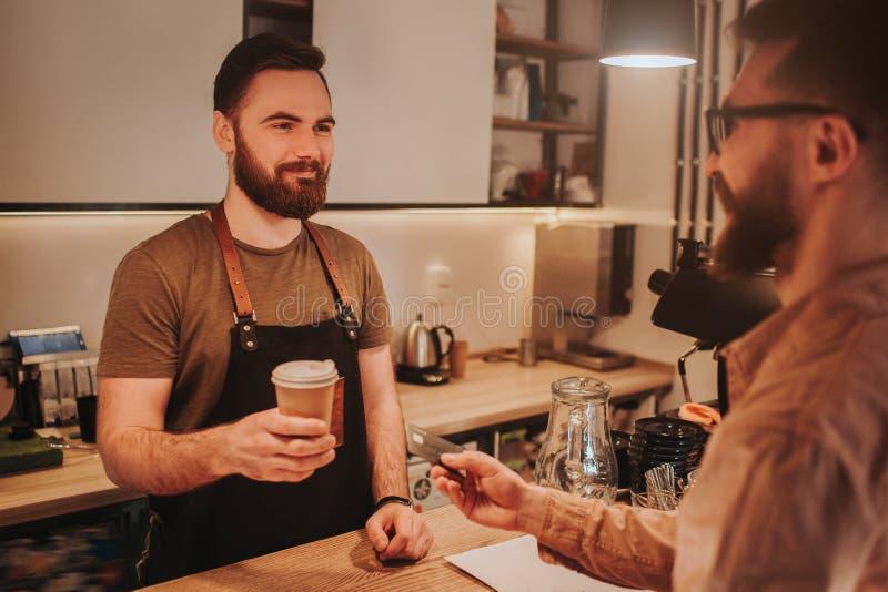 Snittsikt av ett bartenderkläderförkläde och anseende bak tabellen för stång` s och ge en kopp kaffe till kunden På arkivbilder