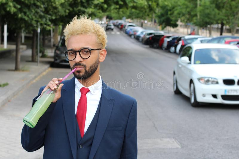 Snobbish afro businessman drinking a soda outdoors.  stock image