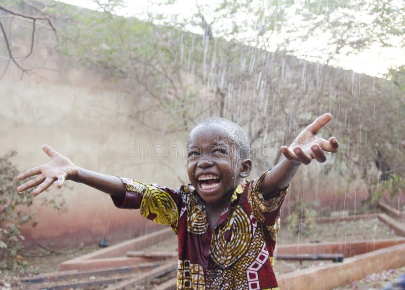 Snoepje weinig Afrikaanse jongen onder de regen in Mali Africa royalty-vrije stock fotografie