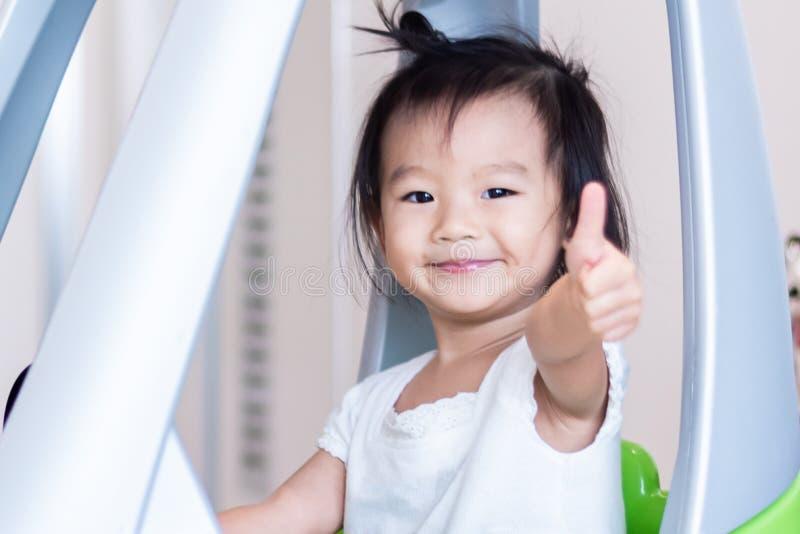 Snoepje Weinig Aziatisch meisje die op kleine die auto met duim berijden omhoog op wit wordt geïsoleerd royalty-vrije stock fotografie