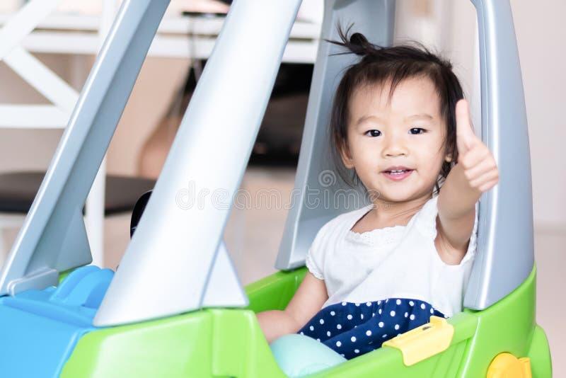 Snoepje Weinig Aziatisch meisje die op kleine die auto met duim berijden omhoog op wit wordt ge?soleerd stock foto's