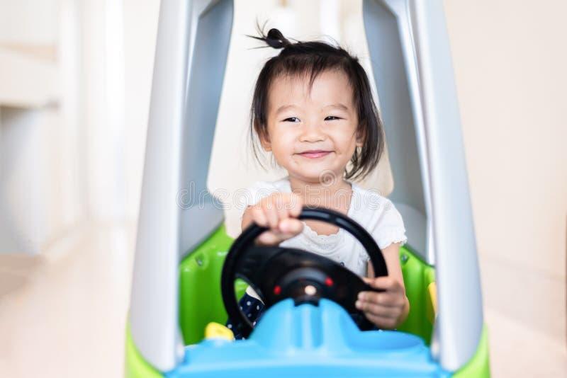 Snoepje Weinig Aziatisch meisje die op kleine auto met het glimlachen berijden stock foto's