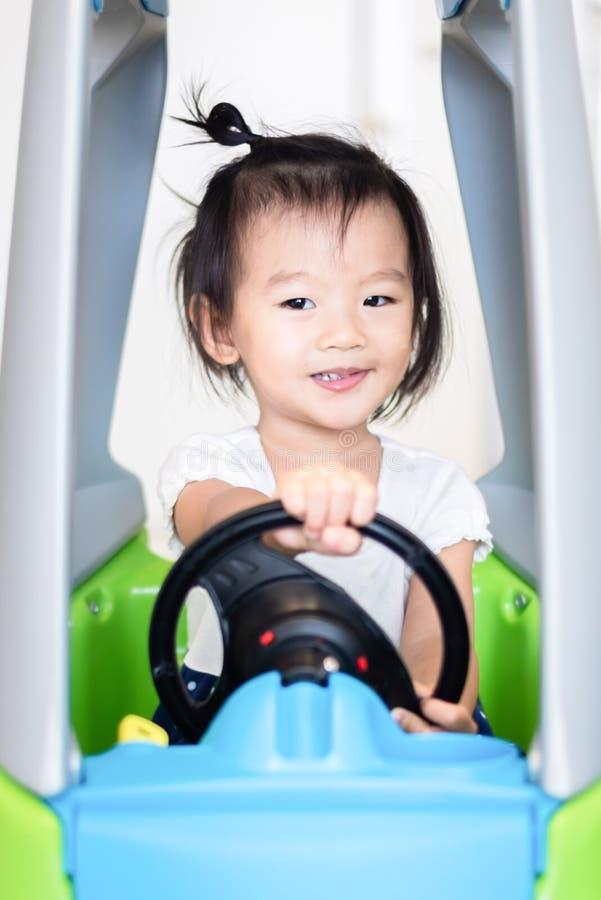 Snoepje Weinig Aziatisch meisje die op kleine auto met het glimlachen berijden royalty-vrije stock afbeeldingen
