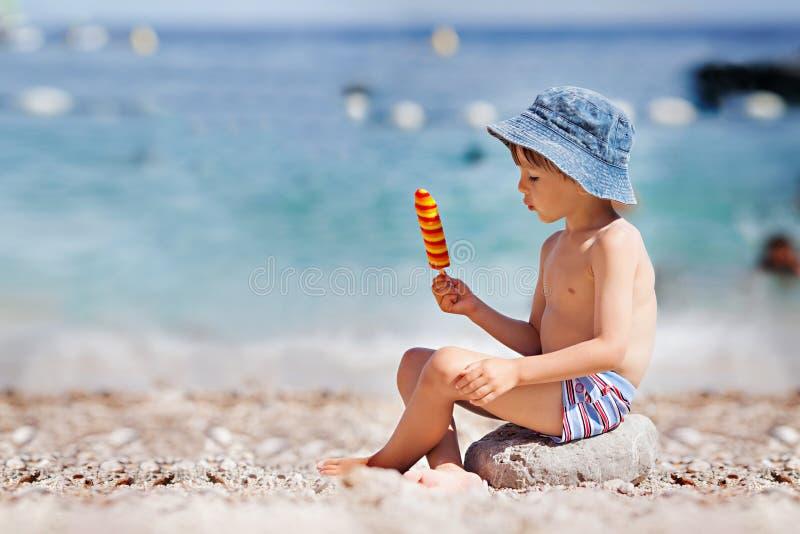 Snoepje weinig kind, jongen, die roomijs op het strand eten stock foto