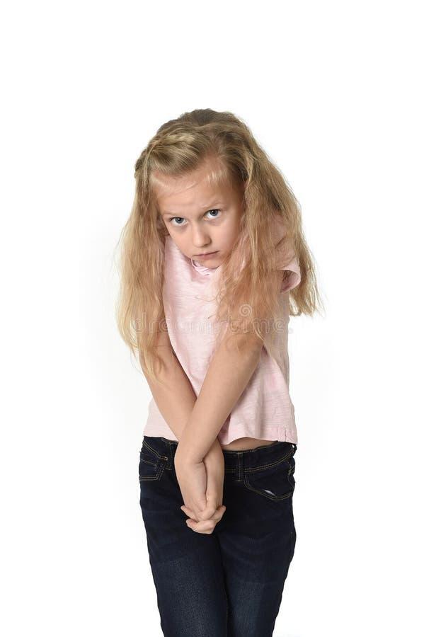 Snoepje weinig kindmeisje die met mooi blondehaar in vrijetijdskleding schuw en schuchter alsof doen schrikken kijken royalty-vrije stock afbeelding