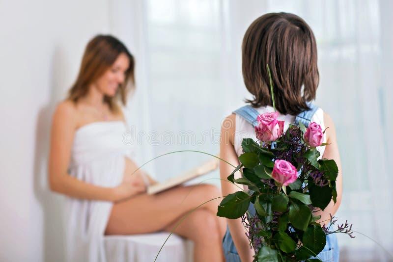 Snoepje weinig peuterkind, jongen, die bloemen geven aan zijn pregnan stock afbeelding