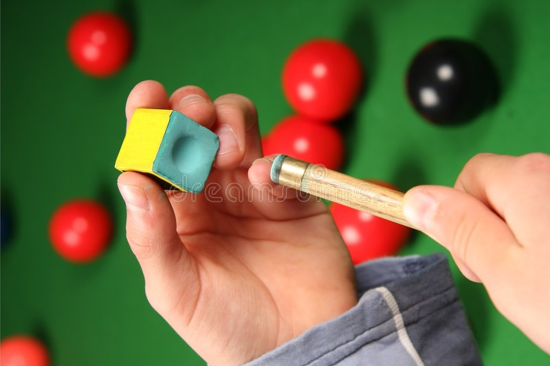 Snooker cue, chalk and hands stock image