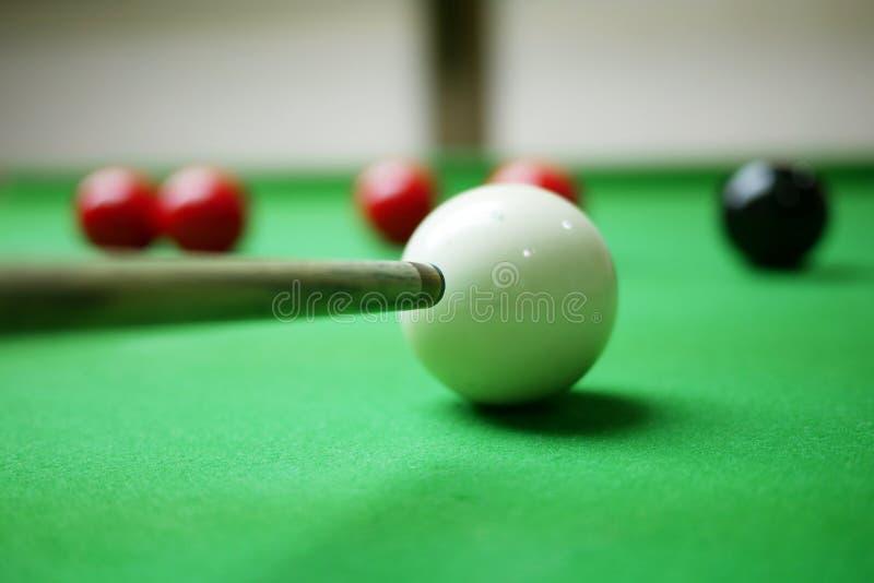 Snookerspelare som siktar på den svarta bollen royaltyfri bild
