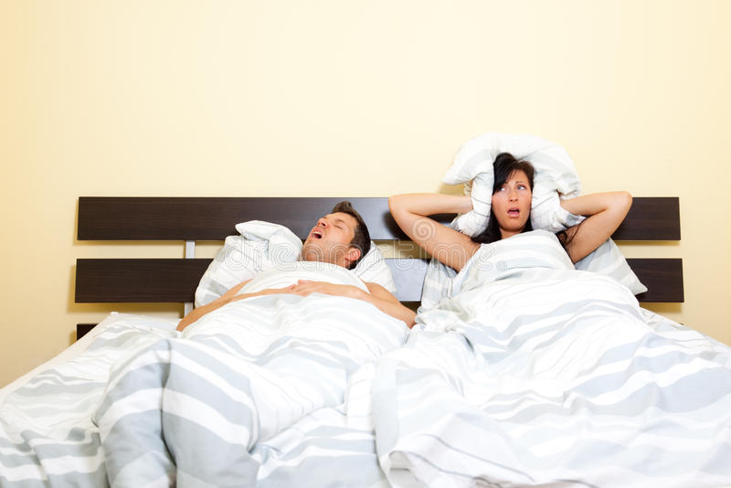 Snorer husband. Scenic in bedroom of pair of loving with young couple lying in bed and holding pillow on the ears because of snoring boyfriend royalty free stock photography