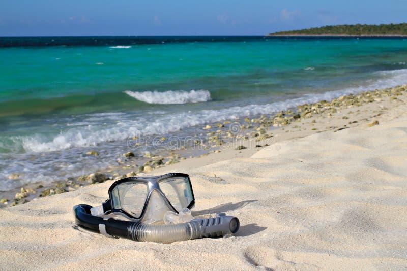 Snorkel och maskering på strandsanden på den havs-/himmelbakgrunden royaltyfria foton
