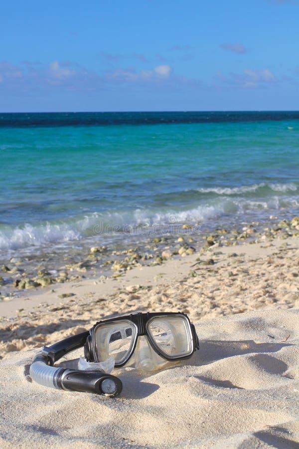 Snorkel och maskering på strandsanden på den havs-/himmelbakgrunden som är sh fotografering för bildbyråer