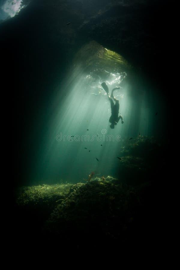 Snorkeler and Sunlight in Dark Raja Ampat Cavern stock photos