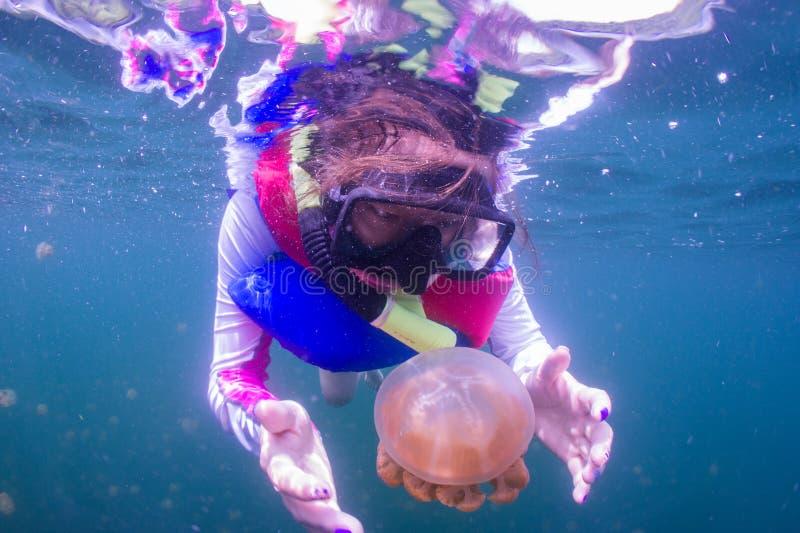 Snorkeling в озере медуз с спасательным жилетом стоковые изображения