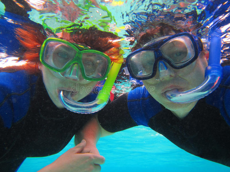 Snorkeling couple. A happy tourist couple snorkeling in blue waters of Rarotonga Island stock image
