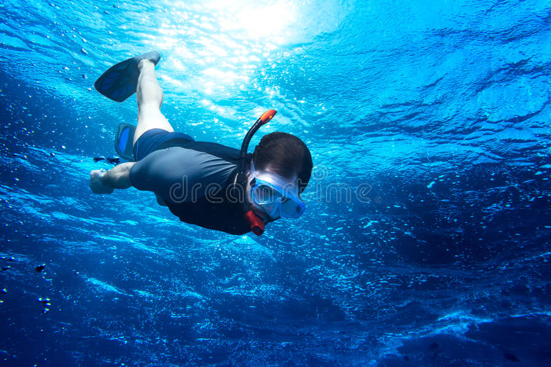 Snorkeling down into the deep blue ocea stock photography