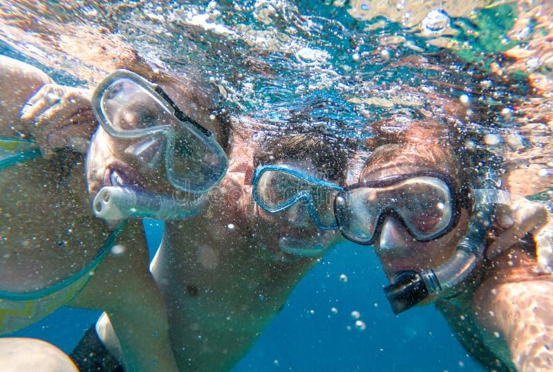 Snorkeling przyjaciół pozować podwodny w wodzie morskiej obrazy stock