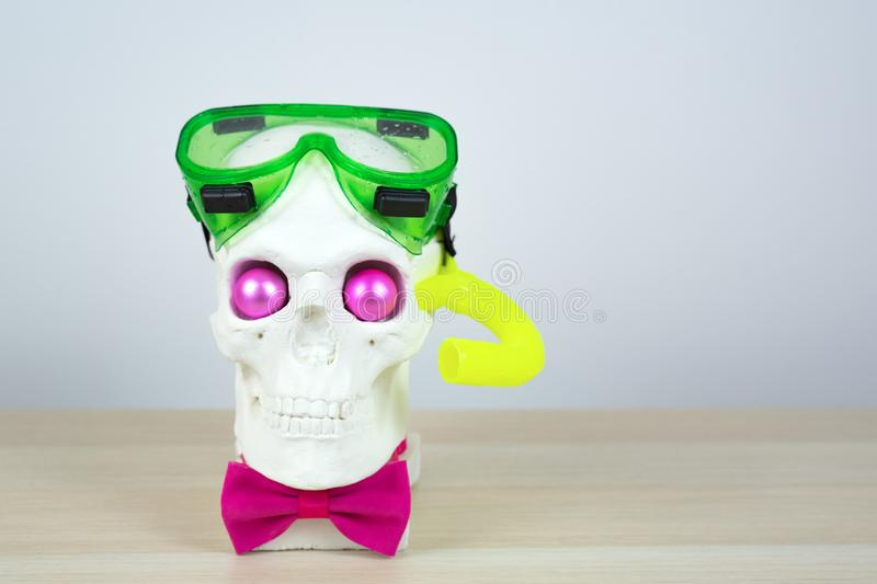Snorkeling scuba diving skull sculpture with pink eyes with mask a yellow tube and a pink bow tie. parody of a scuba diver.  royalty free stock image